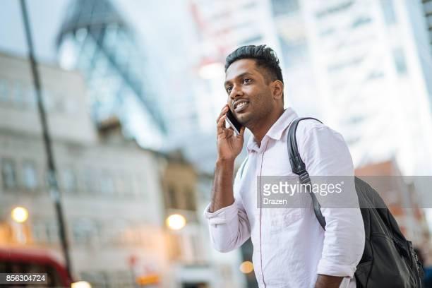 Indischen jungen Mann in London, Überquerung der viel befahrenen Straße beim Multitasking