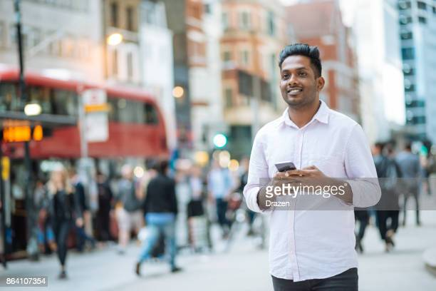 Indian young man in London, crossing the busy street while multi tasking