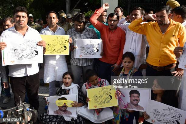 Indian Youth Congress activists shout slogans against Union Minister Dharmendra Pradhan during a protest against petrol hike outside his residence,...