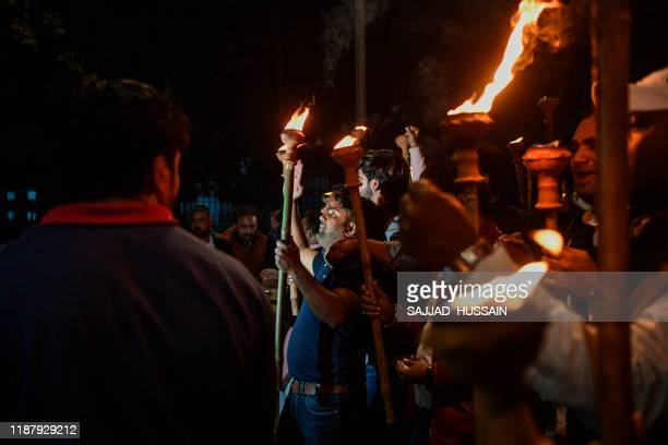 Indian youth congress members hold torches as they shout slogans against the government's Citizenship Amendment Bill during a demonstration in New...