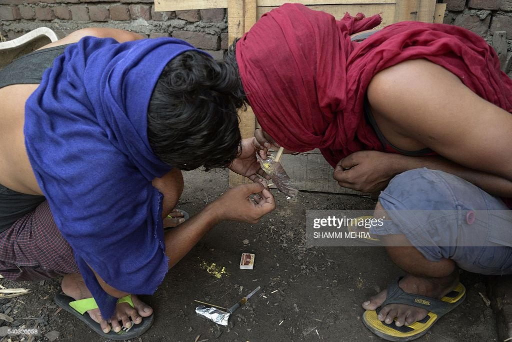 Indian youth inhale drugs on the outskirts of Jalandhar in the north western Punjab province on June 15 2016 / AFP / SHAMMI MEHRA