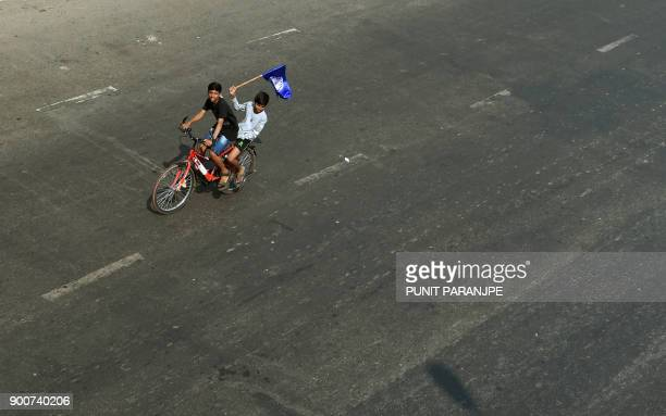 TOPSHOT Indian youths carry Republican Party of India flag during a protest along the Eastern expressway during a protest in Mumbai on January 3 2018...