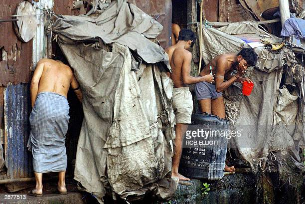 Indian youths clean their teeth near an open sewer in Dharavi slums Bombay 17 January 2004 Poverty of this extreme is a main focus of the World...