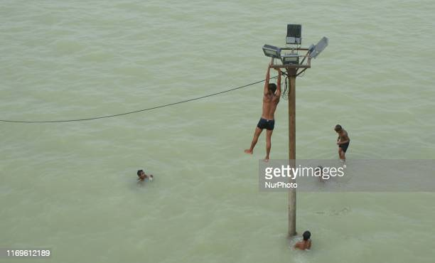 Indian youths dangle from an electric light poll and power line before diving in to the floodwaters of an overflowing Ganges River , in Allahabad on...