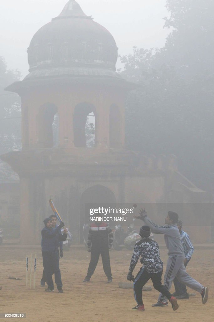 Indian youths play cricket amid heavy fog and air pollution in Amritsar on January 2 2018 / AFP PHOTO / NARINDER NANU