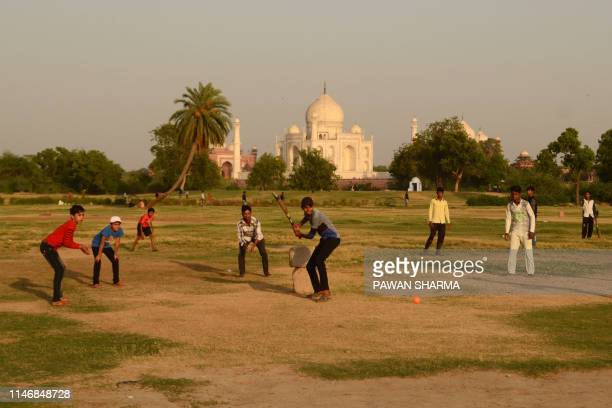 Indian youths play cricket at a park near the Taj Mahal in Agra on May 29, 2019.
