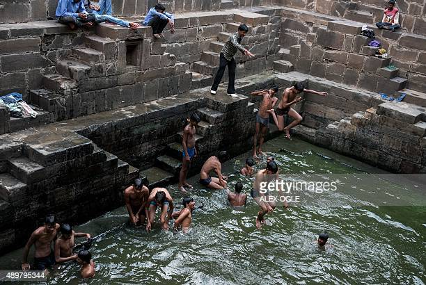 Indian youths play in the water at the bottom of the historic Chand Baori stepwell as others look on in Abhaneri village of western Rajasthan state...