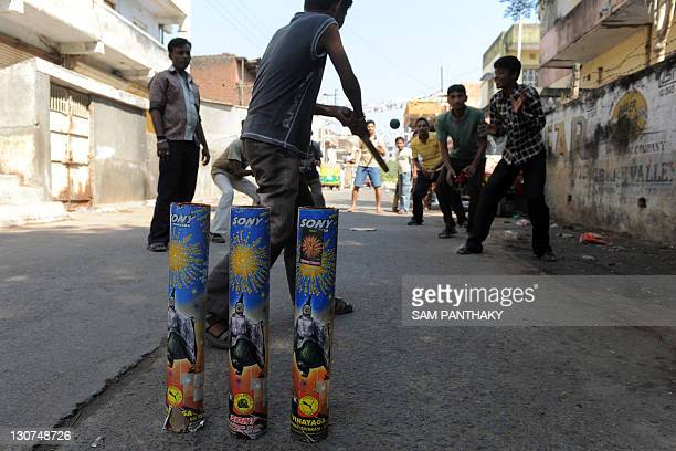 Indian youths play street cricket using spent firecracker shells as improvised stumps in Nadiad town some 60 kms from Ahmedabad on October 29 2011...