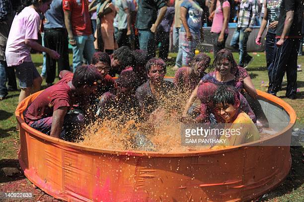 Indian youths splash water coloured with Saffron flowers as they participate in an ecofriendly Holi during 'Rangotsav 2012' at the Chokhi Dhani in...