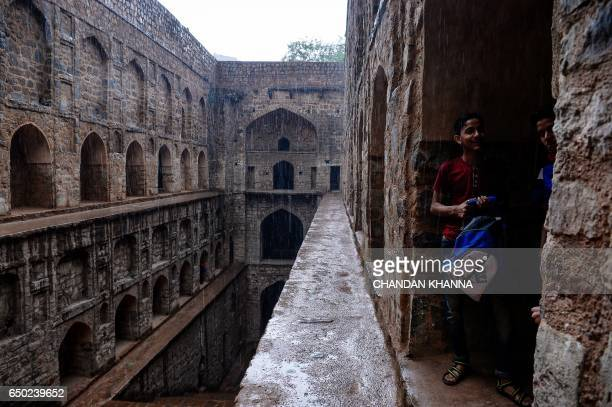 Indian youths take shelter inside the arches of Agrasen ki Baoli during a rainfall in New Delhi on March 9 2017 / AFP PHOTO / CHANDAN KHANNA