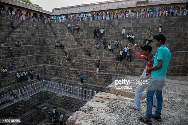 Indian youths throw fruit at their friends in the historic Chand Baori stepwell in Abhaneri village in Rajasthan on September 24, 2015. For a few...