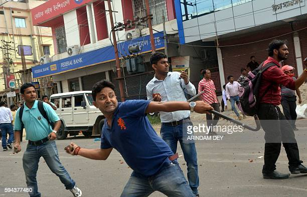 Indian youths throw stones towards Indigeneous People's Front of Twipra supporters in Agartala on August 23 after violence flared in the northeastern...