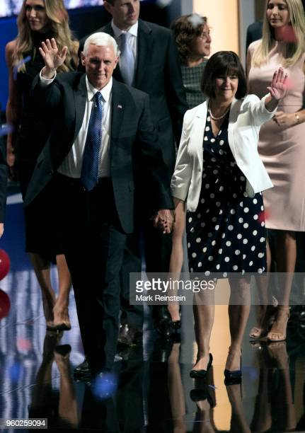Indiana Governor and US vice-presidential candidate Mike Pence and his wife Karen hold hands as they wave from the stage at the close of the...