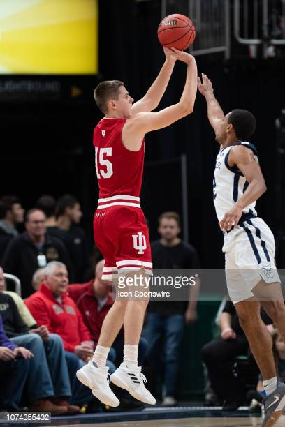 Indiana Hoosiers guard Zach McRoberts shoots a three pointer over Butler Bulldogs guard AaronThompson during the Crossroads Classic basketball game...