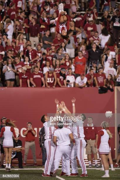 Indiana male cheerleaders throw a female cheerleader high into the air during their season opening college football game between the Ohio State...