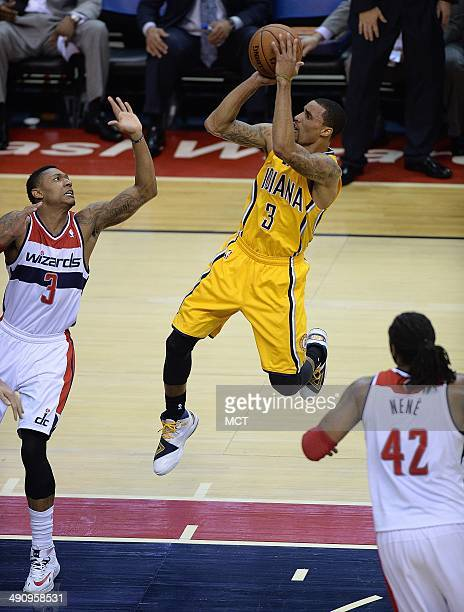 Indiana Pacers guard George Hill shoots between Washington Wizards guard Bradley Beal and forward Nene Hilario during the first half of Game 6 of the...