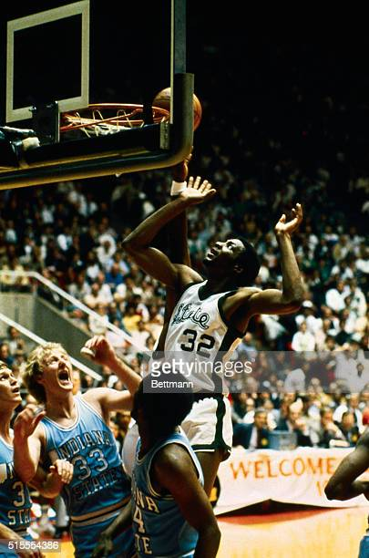 Indiana State's Larry Bird reacts with a yell as he watches Michigan State forward Gregory Kelser helping teammate Earvin Johnson tip in a shot in...