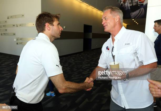 Indianapolis 500 Champion Will Power shakes hands with former Dallas Cowboys fullback Daryl Moose Johnston during a tour at The Ford Center at The...