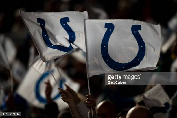 Indianapolis Colts fans wave flags bearing the teamu2019s logo before the game against the Tennessee Titans at Lucas Oil Stadium on December 1 2019...