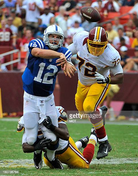 Indianapolis Colts quarterback Andrew Luck comes under pressure from Washington Redskins' Stephen Bowen and Chris Wilson during the first half of a...