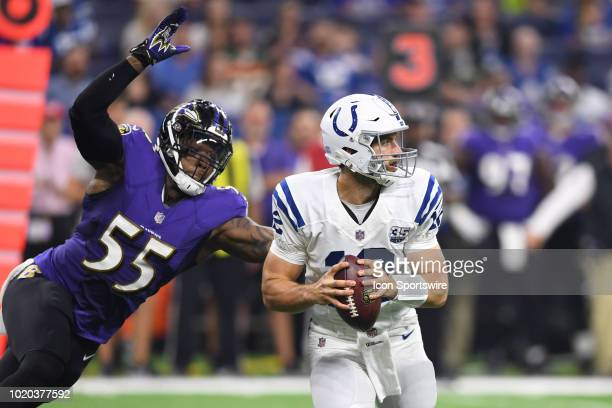 Indianapolis Colts quarterback Andrew Luck holds onto the football as Baltimore Ravens linebacker Terrell Suggs tackles him from behind in action...