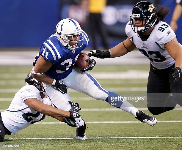 Indianapolis Colts running back Donald Brown tries to get past Jacksonville Jaguars defensive tackle Tyson Alualu and Jacksonville Jaguars cornerback...
