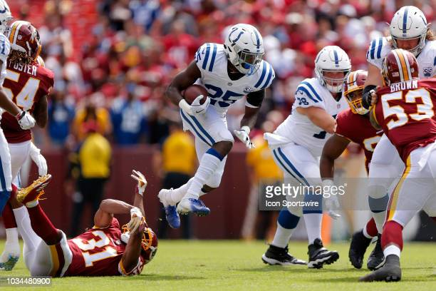 Indianapolis Colts Running Back Marlon Mack jumps over Washington Redskins Cornerback Fabian Moreau during the game between the Indianapolis Colts...