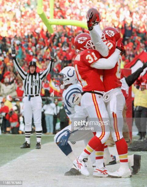 Indianapolis Colts safety David Tate gets to his feet as Kansas City Chiefs runningback Leroy Thompson congratulates receiver Lake Dawson on his...
