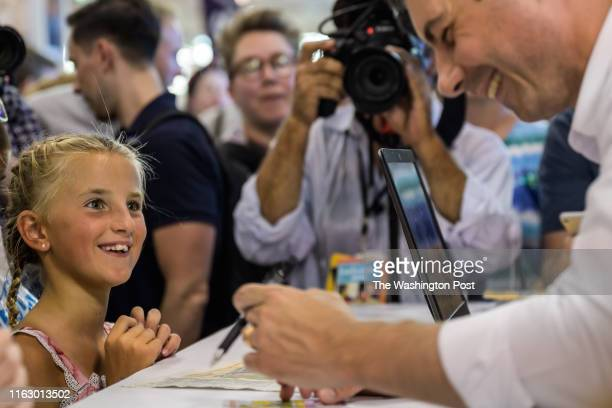 Indiana's South Bend Mayor Pete Buttigieg 2020 Democratic Presidential Candidate signs a young girl photo at the Iowa State Fair on Tuesday August 13...