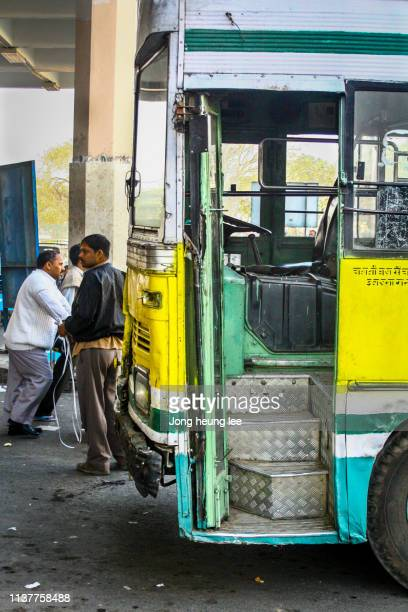 Indians and old yellow bus in India