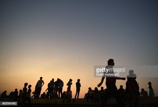 Indians gather at the seafront during sunset in Mumbai on New Year's eve on December 31 2017 / AFP PHOTO / PUNIT PARANJPE