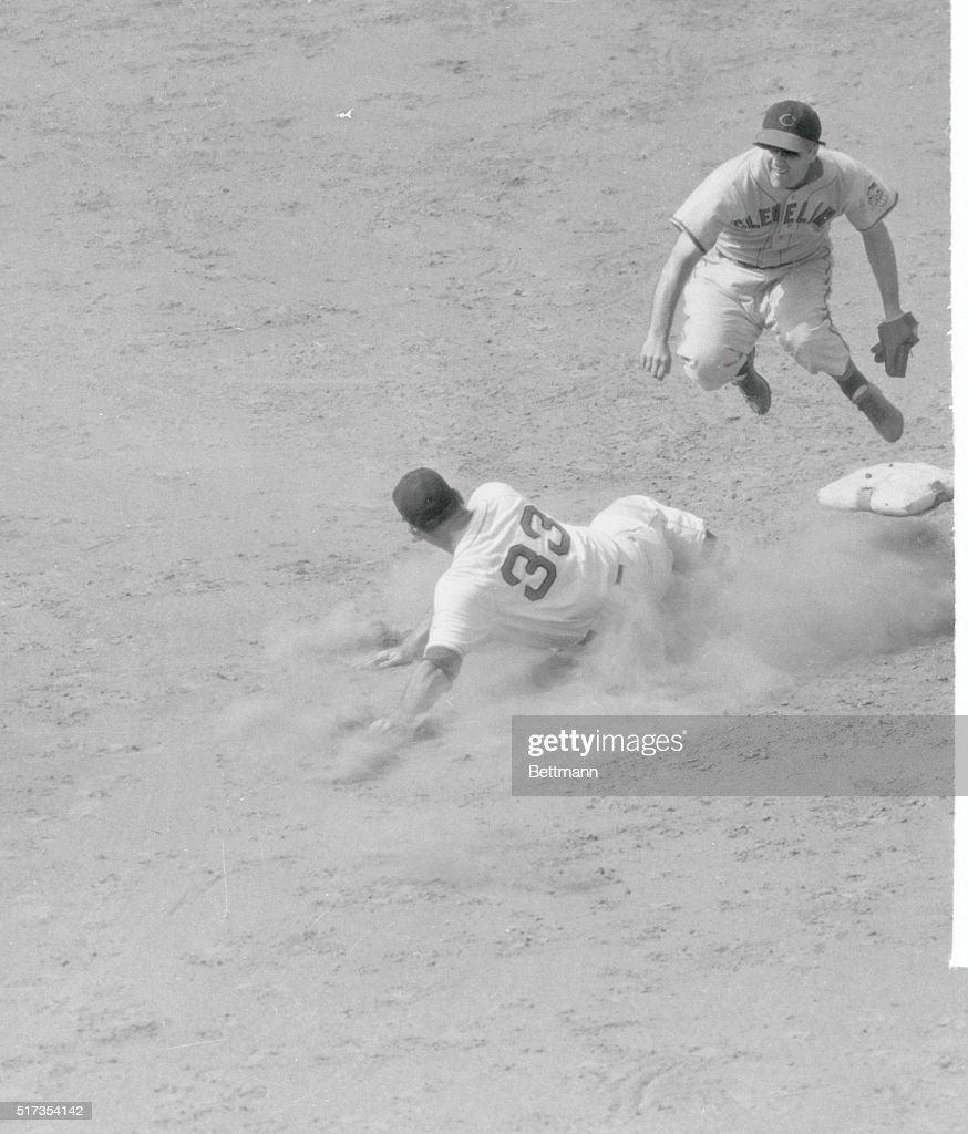 Dave Ferris of the Boston Red Sox raises a cloud of dust as he slides into second in an attempt to break up double play, but shortstop Lou Boudreau, Indians, jumps in the air as he fires to first to complete the twin killing, in third inning of game at Fenway Park. Third baseman Ken Keltner flipped to Boudreau after fielding Dom DiMaggio's grounder.