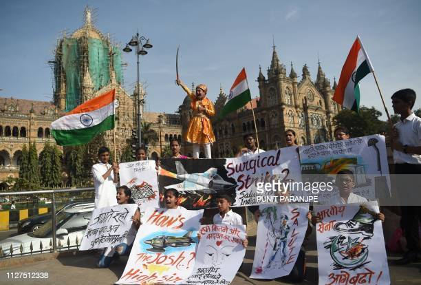 Indians hold placards and national flags as they celebrate the Indian Air Force strike launched on a JaisheMohammad camp at Balakot in front of the...