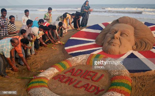 Indians pay tribute beside a sand sculpture of former British prime minister Margaret Thatcher, made by sand artist Sudersan Pattnaik, at the Golden...
