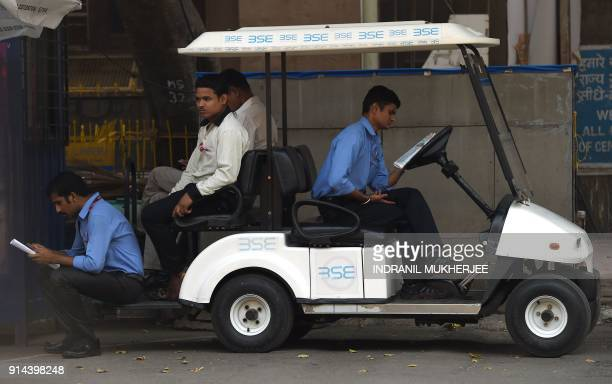 Indians read newspapers sitting on a cart outside the Bombay Stock Exchange in Mumbai on February 5 2018 Most Asian markets tumbled February 5 after...