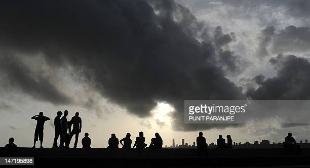 Indians sit near the seafront as dark clouds gather over the city skyline in Mumbai on June 27 2012 Indian agriculture gets 60 percent of its...