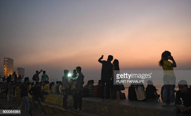 Indians take pictures at the seafront during sunset in Mumbai on New Year's eve on December 31 2017 / AFP PHOTO / PUNIT PARANJPE