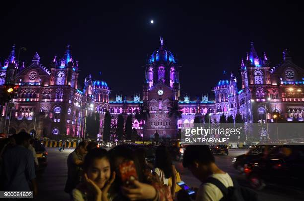 Indians take pictures in front of the lit up Chattrapathi Shivaji Terminus railway station ahead of New Year's eve celebrations in Mumbai on December...