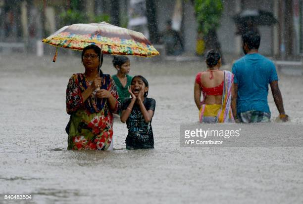 TOPSHOT Indians wade through a flooded street during heavy rain showers in Mumbai on August 29 2017 Heavy rain brought India's financial capital...