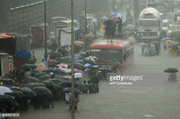 Indians wade through a flooded street during heavy rain showers in Mumbai on August 29 2017 Heavy rain brought India's financial capital Mumbai to a...