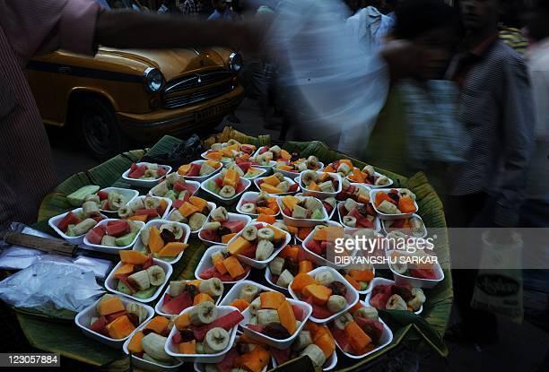 Indians walk past a roadside fruitseller ahead of Eid AlFitr in Kolkata on August 29 2011 Markets across the Muslim world witnessed a huge shopping...