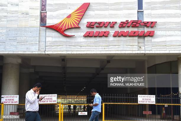 Indians walk past a sign of state carrier Air India outside its headquarters in Mumbai on January 10 2018 Indian lawmakers cleared a proposal in...