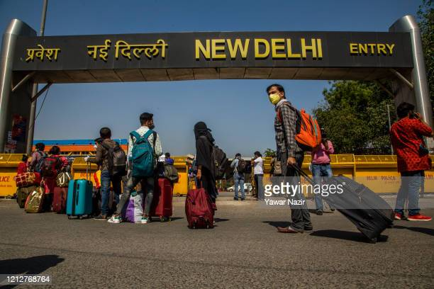 Indians wearing protective masks stand in queue outside a railway station as they wait to board trains that will take them to their native places...
