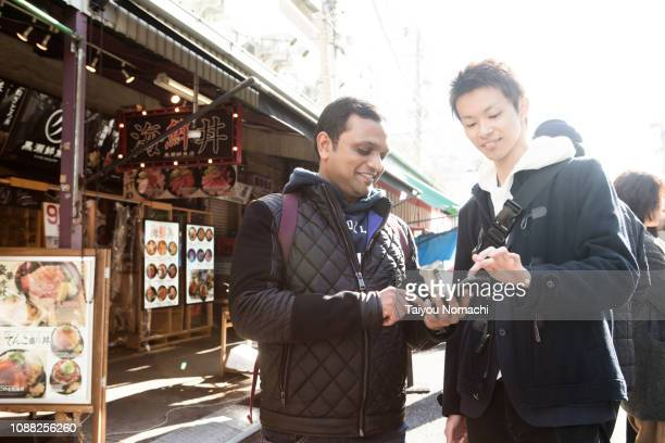 indians who ask the way for japanese people in tsukiji - 観光客 ストックフォトと画像
