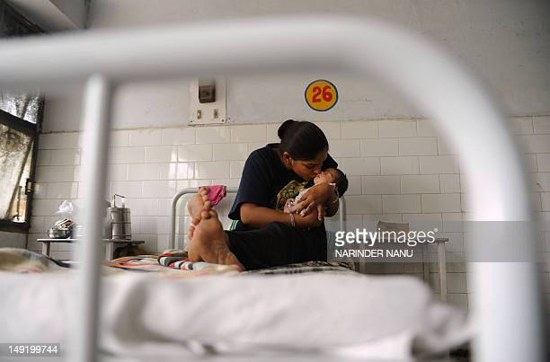 IndiapopulationsocietyhealthwomenFEATURE by Ammu Kannampilly This photo taken on July 5 2012 shows an Indian mother kissing her new born daughter in...