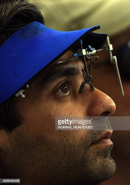 India's Abhinav Bindra looks at his score after the men's 10m air rifle individual event at the Ongnyeon International shooting range of the 2014...