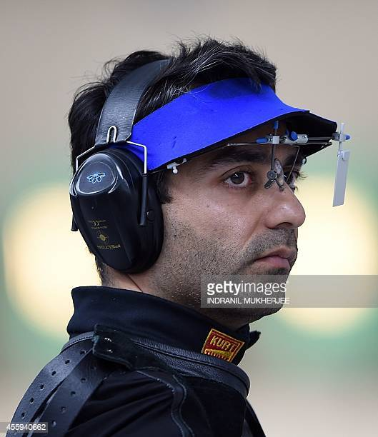 India's Abhinav Bindra looks at the scoreboard during the men's 10m air rifle event at the Ongnyeon International shhoting range of the 2014 Asian...