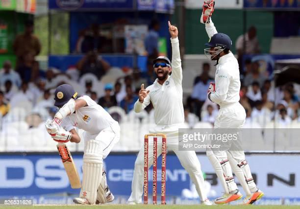 India's Ajinkya Rahane and wicketkeeper Wriddhiman Saha unsuccessfully appeal for a Leg Before Wicket decision against Sri Lanka's Kusal Mendis...