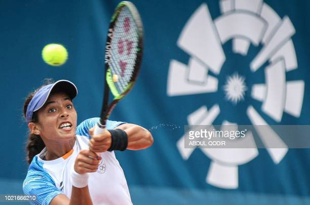 India's Ankita Ravinderkrishan Raina hits a return against China's Zhang Shuai in their women's singles tennis semifinal match at the 2018 Asian...