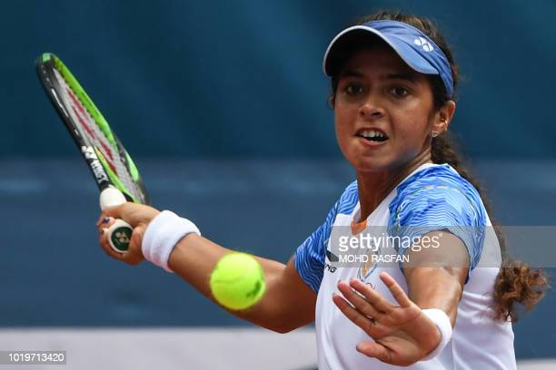 India's Ankita Ravinderkrishan Raina hits a return against Indonesia's Beatrice Gumulya in their women's singles tennis match during the 2018 Asian...
